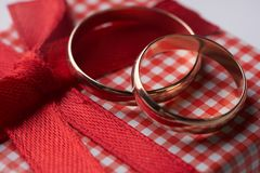 Close-up of two gold Wedding rings and Gift box Royalty Free Stock Images