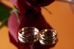 Close-up of two Gold Wedding rings and wedding bouquet. Of red roses on orange mirror background. Gold rings for the bride and groom,  marriage proposal Stock Photo