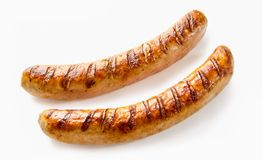 Close-up of two grilled German sausages on white. Studio shot close-up of two grilled German sausages on white background for copy space stock images