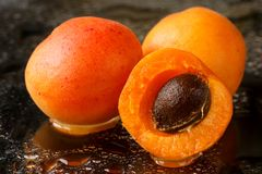 Close up of two and a half sliced apricot fruits with the stone, freshly washed with water drops on a dark background Royalty Free Stock Images