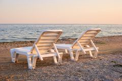 Close up two half-turn chaise longues on the sand. Concept of tranqil evening on the sea beach with two chaise longues Royalty Free Stock Photo