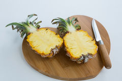 Close-up of two halved pineapple on chopping board Royalty Free Stock Image