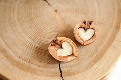 Close-up two halves of walnut in shape of heart on wooden background. Top view. stock photography