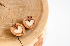 Close-up two halves of walnut in shape of heart on wooden stump royalty free stock images
