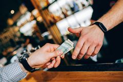 Close up of two hands. The customer`s hand is giving some cash to a barman`s hand for the drink. Cut view. Close up of two hands. The customer`s hand is giving stock image
