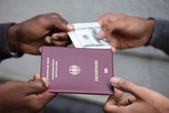 Hands Exchanging Passport For Banknote. Close-up Of Two Hands Exchanging Passport For Us Dollar Notes royalty free stock photography