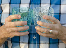 Close up of two hands holding plastic cups. Close up of a married man's hands holding two plastic cups one is light blue and the other is a teal. Background is Stock Photos