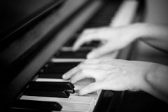 Close up of two hands playing piano, shallow focus. Black and white. Photography stock photo