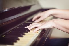 Close up of two hands playing piano, shallow focus. Art background royalty free stock image