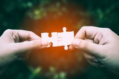 Close up of two hands trying to connect couple puzzle piece. With forest background; one part of whole; symbol of association and connection for business Royalty Free Stock Images