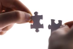 Close up of two hands trying to connect puzzle pieces. Stock Photos