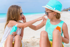 Close-up two kids take care of each other. Kids applying sun cream to each other on the beach. The concept of protection. Sister applying sun cream to sister Royalty Free Stock Images