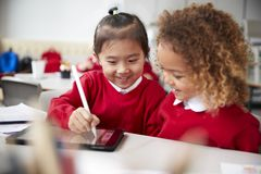 Close up of two kindergarten schoolgirls wearing school uniforms, sitting at a desk in a classroom using a tablet computer and sty. Lus, looking at the screen royalty free stock image
