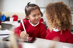 Close up of two kindergarten schoolgirls wearing school uniforms, sitting at a desk in a classroom using a tablet computer and sty. Lus, looking at each other royalty free stock photo