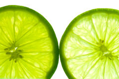Close-up of two lime slices. Two green lime slices, backlit and isolated on white background Royalty Free Stock Images