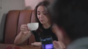 Close up of two male friends resting in the restaurant showing video on the cellphone to each other. Attractive bored. Girl sitting in front of them drinking stock video footage