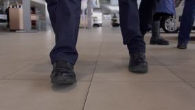 Close up of two male legs walking throught autocenter, slow motion. Close up of two male legs walking throught autocenter. Concept: people, business, auto stock footage