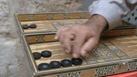 Close up of two men playing a game of arabic backgammon in the muslim quarter of the old city