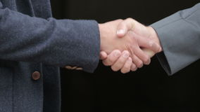 Close-up of two men shaking hands. Close-up of two men in suits shaking hands stock video