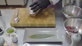 Close up two metal bowls in the cutting board with cutted salmon and tuna fish. Hands in black latex gloves prepare food. Two metal bowls in the cutting board stock video