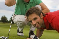 Close-up of two mid adult men playing golf in a golf course and smiling Royalty Free Stock Images