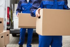 Close-up Of Two Movers Carrying Cardboard Box. Close-up Of Two Mover`s Hand In Uniform Carrying Cardboard Box royalty free stock photo