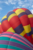 Close up of two Multi colored Hot air balloons. Against a blue cloudy sky royalty free stock photo