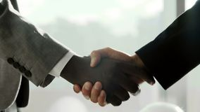 Close up Two multiethnic business partner shake hands when meeting in front of large panoramic window in modern bright. Office stock footage