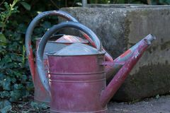Close up on two old weathered and rusty watering cans. Standing on an old cemetery in Germany Royalty Free Stock Images