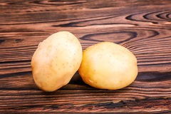Close up of two organic new light brown potatoes on a dark brown wooden table. Fresh organic new potatoes. Young potatoes. Stock Image