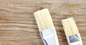 Close-up of two paint brushes. On wooden table stock video