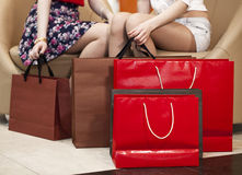 Close up, Two pairs of female legs with shopping bags Stock Images