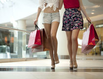 Close up, Two pairs of female legs with shopping bags in their h Royalty Free Stock Photography