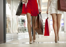 Close up, Two pairs of female legs with shopping bags in their h Royalty Free Stock Photos