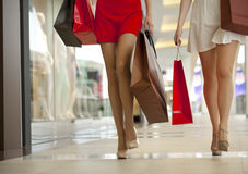 Close up, Two pairs of female legs with shopping bags in their h. Two pairs of female legs with shopping bags in their hands Royalty Free Stock Photos