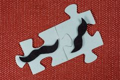 Close-up of two parts of puzzle. Symbolic men with a mustache. The concept of psychological compatibility, friendship. Stock Photo