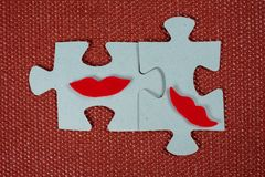 Close-up of two parts of puzzle. Symbolic women with lips. The concept of psychological compatibility, friendship. Stock Images