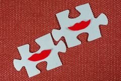 Close-up of two parts of puzzle. Symbolic women with lips. The concept of psychological compatibility, friendship. Stock Photo