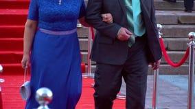 A woman in a blue dress is walking alongside a man in a formal suit, on the red carpet