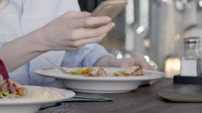 Close up of two people, who are eating salad in the restaurant, slow motion. White plates with delicious dish are standing on wooden table and people are using stock video footage