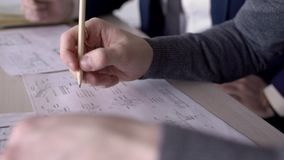 Close-up of two people working on a desk over a paper design project. Engineers` hands together on table construct blueprint using paper and a pencil when stock video footage