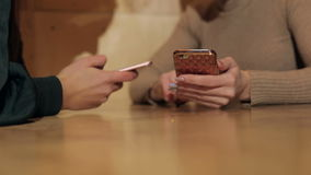 Close-up of two phones in hands of women in cafe. Close-up of two phones in the hands of women in a cafe on wooden brown background stock video footage