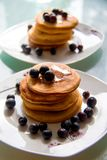 Close up of two plates with towers of tasteful cinnamon pancakes topped with fresh blueberries and maple syrup, sweet and tasty stock image