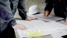 Close up of two professional engineers making construction project drawings. Two men working with sheme of future. Close up of two professional engineers stock video