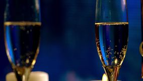 Close up on two rotating flutes of champagne