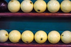White billiard balls on shelf close. Close up two rows of white billiard balls for playing pool lying on shelves Royalty Free Stock Photos
