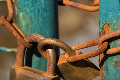 Close up on two rusty and weathered padlocks. Close up on two rusty and weathered padlocks and chains holding a turquoise gate shut Royalty Free Stock Images