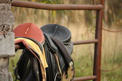 Close up of two saddles on the fence Royalty Free Stock Photos