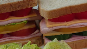Close-up of two sandwiches with bacon, salami, prosciutto and fresh vegetables stock footage