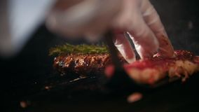 Close up of two slices of meat of varying degrees of readiness lie on the grill, chef turning over one of them. Cooking and Haute cuisine concept stock video
